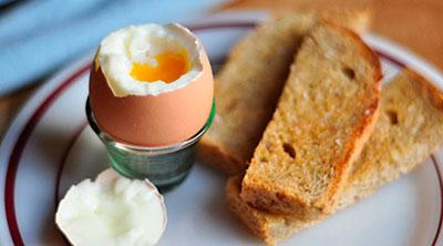 Huevo cocido con pan integral tostado y una pieza de fruta