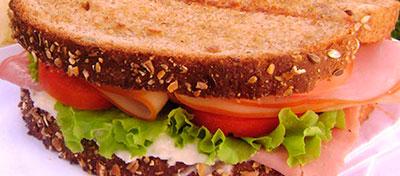 Sandwich de pan integral con pavo, lechuga y tomate y un zumo de naranaja