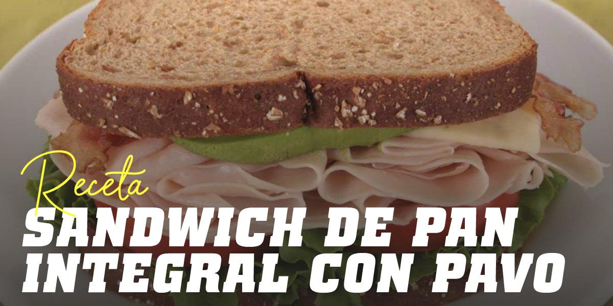 Sandwich de pan integral con pavo, lechuga y tomate y un zumo de naranja