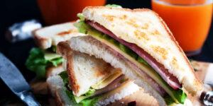 Sandwich de pão integral com peru, alface e tomate e um sumo de laranja