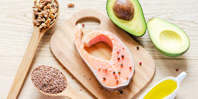 Salmon, walnuts, avocado, seed and oil on a table