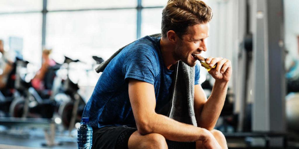 Man eating a bar at the gym