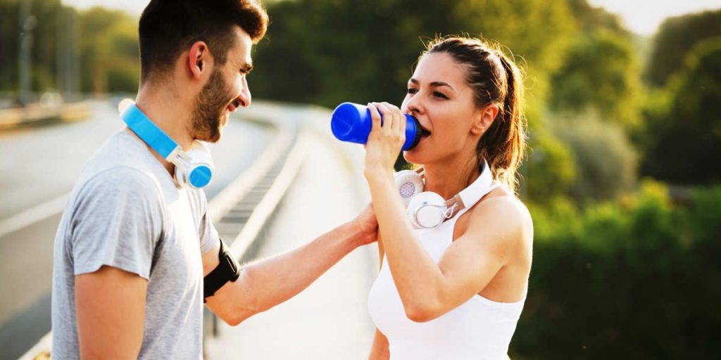 Couple working out and drinking