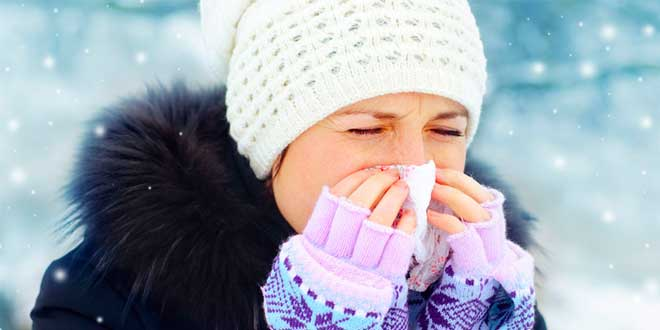 Woman sneezing during winter