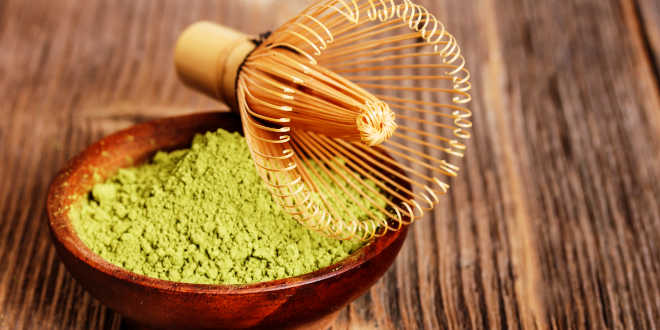 A bowl of matcha powder with a whisk