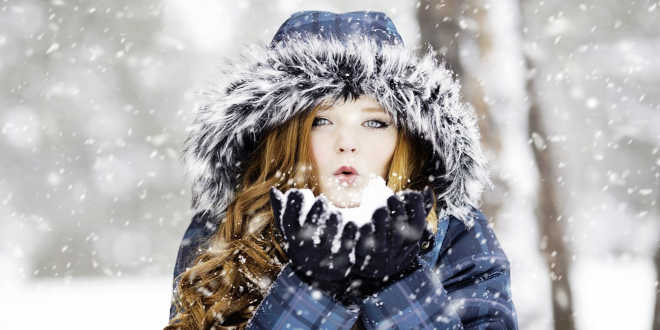 Woman blowing snow in the winter
