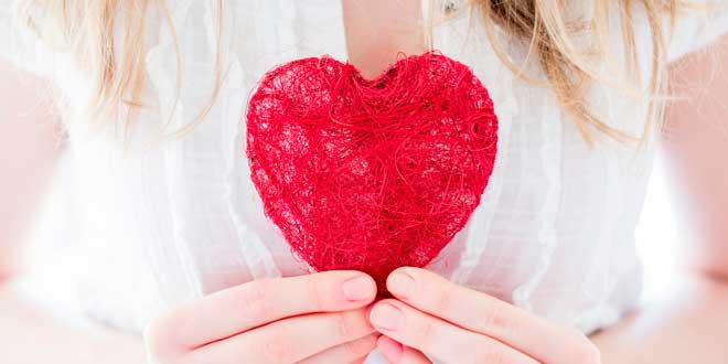 Woman holding a heart made with thread
