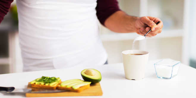 A man making breakfast and putting some xylitol on a coffee