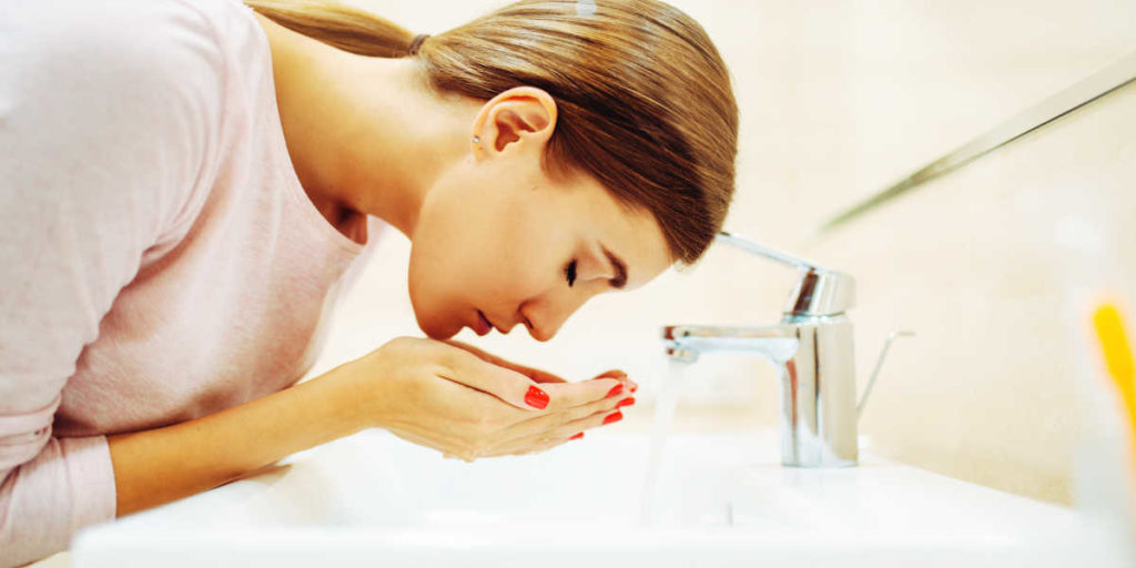Woman washing her face on the sink