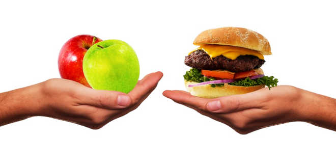 Hand holding two apples and hand holding a hamburguer