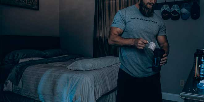 A man making a protein shake in his bedroom