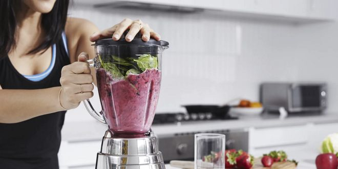 Woman making a smoothie with a blender