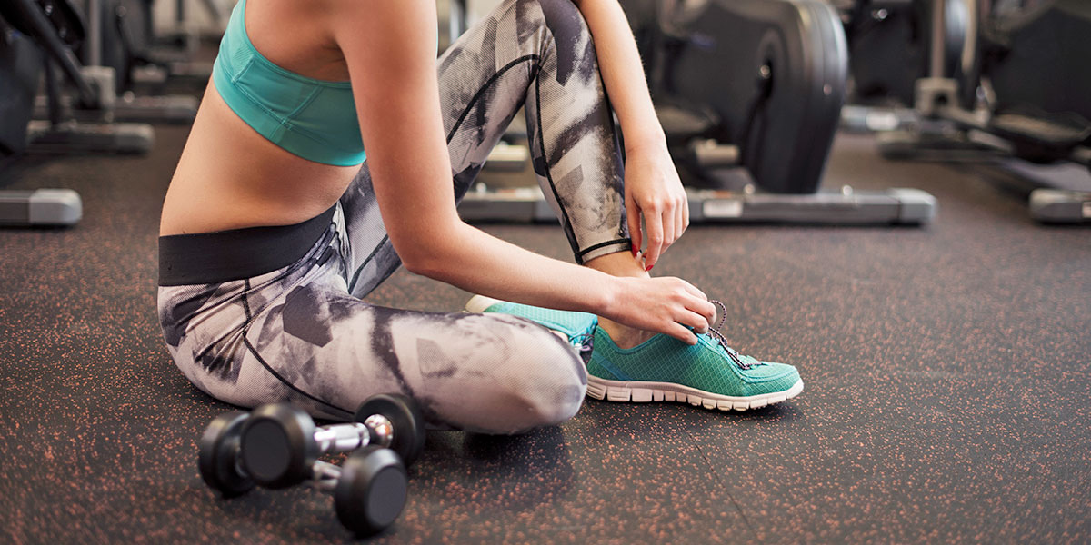 Woman tying her shoes at the gym